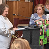 (Brad Davis/The Register-Herald) Minden resident Kimberly Duncan, left, shares her family's experience with cancer as neighbor Angela Coffman holds posters with family photos during the comment portion of a public meeting between town residents and officials from state and federal agencies tasked with investigating the presence of PCB's there Friday night at New Beginning Apostolic Church.