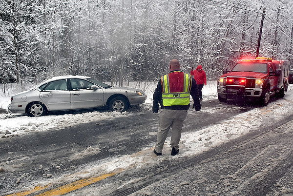 (Brad Davis/The Register-Herald) Firefighters from Coal City and Lester fire departments pull a vehicle from the snow after losing control in deep slush and sliding off Route 54 near Slab Fork Road Saturday evening. There were no injuries.