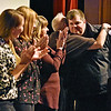(Brad Davis/The Register-Herald) Beckley Police Corporal Ryan Cuevas, far right, gets a big hug from Women's Resource Center executive director Patricia Bailey after receiving an Incite Hope award from the organization during their 28th Annual Candlelight Vigil Thursday night inside The Raleigh Playhouse & Theatre.