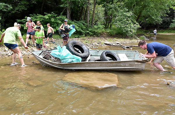 (Brad Davis/The Register-Herald) A team of creek hikers consisting of members of Active Southern West Virginia and the Coal River Mountain Watch haul a boat full of garbage pulled from a section of the Peach Tree Creek and falls areas during a cleanup effort Saturday afternoon near Naoma.