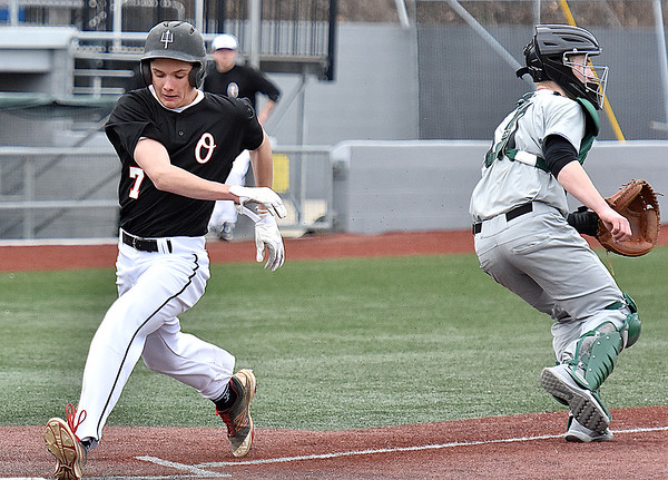 (Brad Davis/The Register-Herald) Oak Hill's Preston Legg, left, dodges Wyoming East catcher Eric Hoosier to score a run Friday evening at Linda K. Epling Stadium.