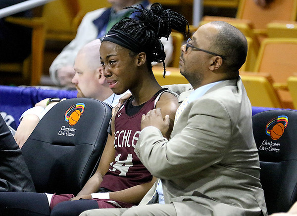 (Brad Davis/The Register-Herald) Woodrow Wilson senior Sydni Darden in consoled on the bench by assistant coach Kevin Henry after fouling out late in the Lady Eagles' close loss to Parkersburg South Wednesday afternoon at the Charleston Civic Center. Darden was strong in her final game in a Woodrow uniform, scoring 10 points, grabbing six rebounds and three steals.