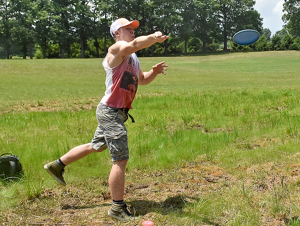 (Brad Davis/The Register-Herald) Disc golfer Dylan Buckland throws from the fairway on hole #9 of a brand new disc golf course at Daniel Vineyards Friday afternoon.