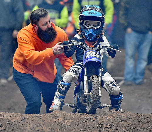 (Brad Davis/The Register-Herald) A course crew member pushes young racer and Salt Rock native Ryder Smith up and over the tall finish line double section, a routine thing to see in the four through eight-year-old division, during the weekend's Tristate MX dirt bike racing event Saturday night at the Beckley-Raleigh County Convention Center.