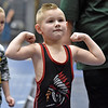 (Brad Davis/The Register-Herald) Four-year-old Jase Turner, a U-4, 45 pound weight class grappler who goes to Holden Elementary in Logan County, flexes the guns for fans and family in the stands as hundreds of young wrestlers from all over the state are introduced Sunday afternoon at Beckley-Raleigh County Convention Center.
