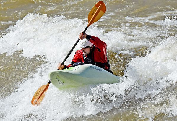 """Tom Gerencer, from Fayetteville, hits a wave on his Kayak at """"The Dries"""" on the New River during an un-seasonably warm day that saw temperatures in the high 70s on Tuesday. (Chris Jackson/The Register-Herald)"""