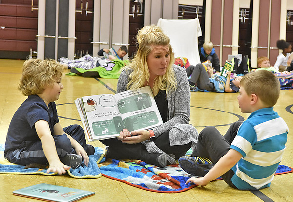 (Brad Davis/The Register-Herald) Crescent Elementary School Pre-K teacher Mary Beth Garcia reads to students Carson Croaston, left, and Kayden Asbury during the school's Read-a-Thon fundraiser Wednesday afternoon. The event was a different take on fundraising where every child got sponsors and collected donations in the hopes of raising a combined $5,000 towards playground equipment and other support items. Participating students then gathered Wednesday in the gym with a pillow and blanket to cozy up with as they read and were read to by their teachers.