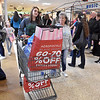 (Brad Davis/The Register-Herald) Ike's Fork residents Madison Martin, left, and Vicki Cline, to Martin's right, wheel their big haul of holiday goodies along as they and swarms of other shoppers cash in on Black Friday sales inside the Crossroads Mall yesterday afternoon.