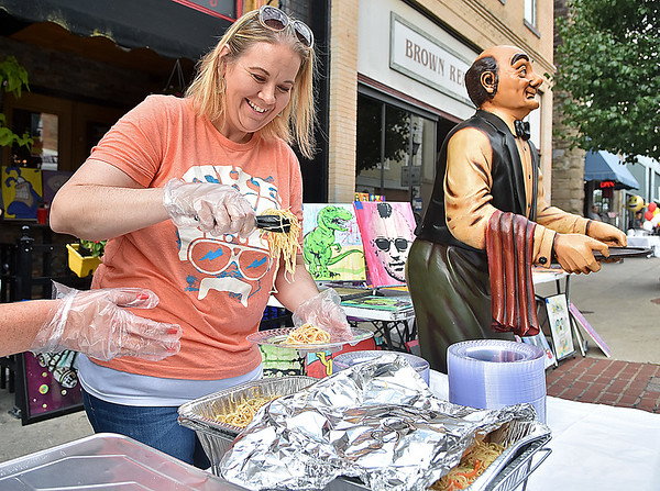 (Brad Davis/The Register-Herald) Employee Crystal Foster Jones prepares plates of Asian pasta salad as she and other volunteers man the Foster's (no relation) Main Street Tavern booth during Taste of Beckley Saturday evening.