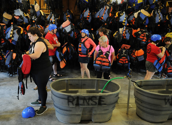 Rafters with the Tragedy Assistance Program for Survivors (TAPS), a retreat that welcome families who have lost a loved one as a result of their military service, get suited up with their gear before heading out to whitewater rafter the lower New River art AOTG in Lansing on Friday. (Chris Jackson/The Register-Herald)