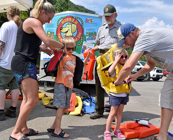 (Brad Davis/The Register-Herald) Young Hinton residents Jace Richmond (left), 7, and sister Sadie, 5, get fitted with the right sized life jackets prior to a boat ride by parents Justin and Kristin Richmond as National Park Service's Richard Altare helps find the right ones during the annual Safety on the Blue event Sunday afternoon at Bluestone lake.