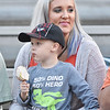 Katy Judy, from Talcott, holds her son, Jace, 3, as he eats a candy apple prior to Summers County's game against Shady Spring Friday in Hinton. (Chris Jackson/The Register-Herald)