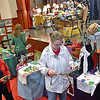 (Brad Davis/The Register-Herald) Patrons browse various art works, clothing items and wares from all-local vendors inside the packed stage area at The Raleigh Playhouse & Theatre during Small Business Saturday.