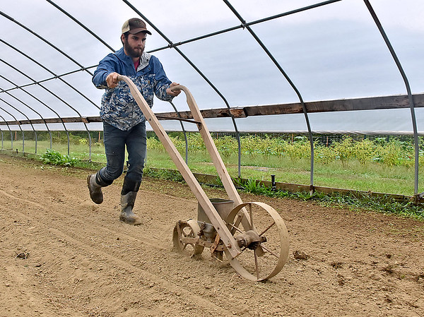 (Brad Davis/The Register-Herald) Sprouting Farms production manager Lucas Hilsbos performs a demonstration on proper farming equipment techniques during a WV CRAFT (Collaborative Regional Alliance for Farmer Training) open house style event Sunday afternoon in Talcott.