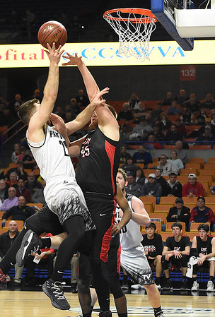 Levi Davis, of Tug Valley, left, shoots over Billy Dillinger, of Greater Beckley Christian during the quarter-final game of the Class A Boys State Basketball Tournament held at the Charleston Civic Center. Tug Valley won 83-52<br /> (Rick Barbero/The Register-Herald)