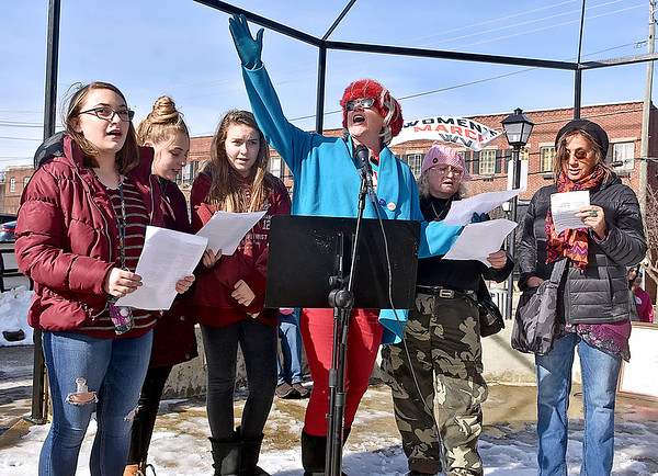 """(Brad Davis/The Register-Herald) Concerned citizen and activist DL Hamilton, middle, enthusiastically leads the crowd in song during the """"It's Our Time"""" rally marking the one-year anniversary of the Women's March Saturday morning in Beckley's Showmaker Square."""