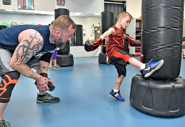 (Brad Davis/The Register-Herald) Five-year-old Carson Ballard works on his kick technique with encouragement from instructor Jamie Jesse during the first Kids Combat Cardio session to be held Sunday afternoon at the YMCA of Southern West Virginia. The one hour class will be held every Sunday in two age groups, kids 5-10 at 3:00 p.m., kids 11-18 at 4:00 p.m. and combines a fun workout environment with basic mixed martial arts training and techniques.