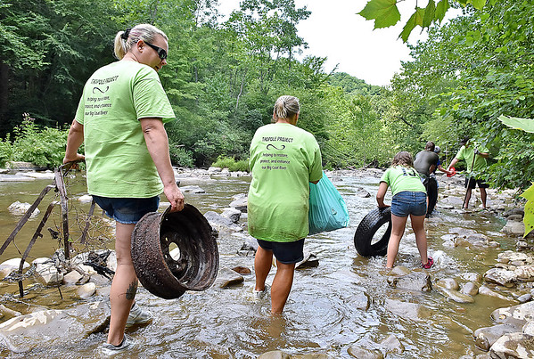 (Brad Davis/The Register-Herald) A team of creek hikers consisting of members of Active Southern West Virginia and the Coal River Mountain Watch haul garbage pulled from a section of the Peach Tree Creek and falls areas during a cleanup effort Saturday afternoon near Naoma.