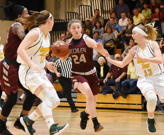Woodrow Wilson's Elizabeth Cadle (24) dribbles through Greenbrier East's Abby Bartenslager (10) and Autumn Hill (13) during the first half of their basketball sectional championship game in Lewisburg Friday. (Chris Jackson/The Register-Herald)