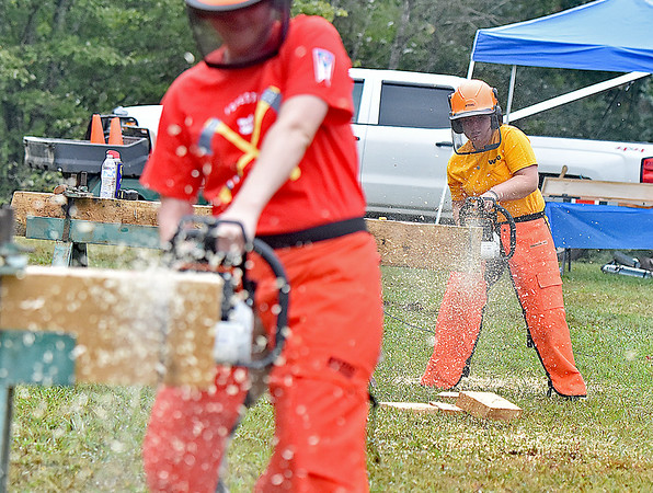 (Brad Davis/The Register-Herald) WVU Woodsman Team member Asthon Stevenson, right, competes one-on-one against Ohio State's Forestry Forum team member Katie Reiderman (foreground left) during the Lumberjack Competition at the annual Lumberjackin' Bluegrassin' Jamboree Saturday morning at Twin Falls State Park.