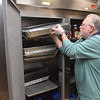 (Brad Davis/The Register-Herald) Lead pastor Steve Hamrick puts full pans of chopped ham and turkey into a giant fridge as a crew of fellow members prepare United Methodist Temple's annual Community Christmas Dinner Saturday night inside The Place. As they do every year, United Methodist Temple will utilize an army of volunteers young and old to feed well over 500 people in the area, and anyone is welcome. The dinner begins at 11:00 a.m. at The Place and runs until 2:00 p.m.