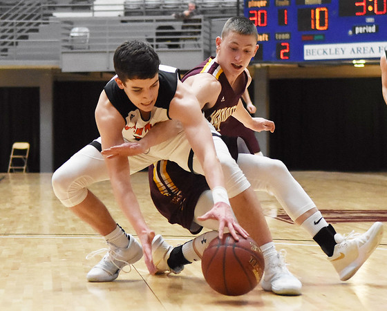 Richwood's (14) and Pocahontas County's Logan Dilley (12) dive for a loose ball during the first quarter of their Big Atlantic Classic basketball game Monday in Beckley. (Chris Jackson/The Register-Herald)