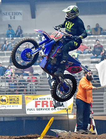(Brad Davis/The Register-Herald) Fayetteville resident Shawn Laughery catches air on the finish line double section of the course as he competes during the weekend's Tristate MX dirt bike racing event Saturday night at the Beckley-Raleigh County Convention Center.