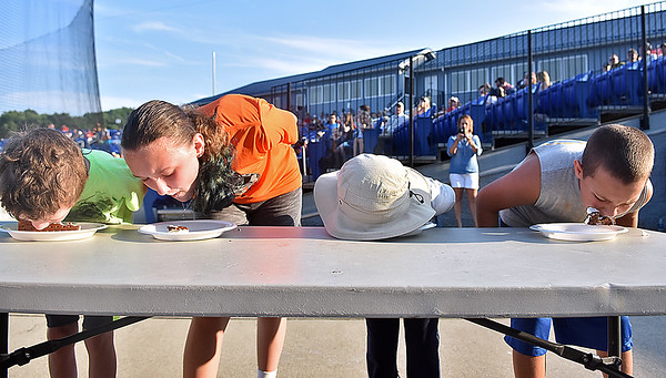 (Brad Davis/The Register-Herald) From left, Preston Lanna, 8, sister Madalynn, 13, Kilian Willis, 6, and eventual champion Easton Dickenson, 11, battle through the ice cream headaches to compete for glory in a between-innings ice cream sandwich eating contest during the Miners game against the Chillicothe Paints Saturday evening at Linda K. Epling Stadium.