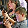 (Brad Davis/The Register-Herald) Family member use smartphones to capture the moments of Summers County High School's graduation ceremony Friday evening in Hinton.