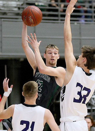(Brad Davis/The Register-Herald) Wyoming East's Roy Hood passes off a drive as James Monroe's McKiney Mann (#33) defends during Big Atlantic Classic action Wednesday night at the Beckley-Raleigh County Convention Center.