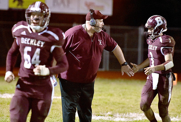 (Brad Davis/The Register-Herald) A pumped up Woodrow Wilson head coach Street Sarrett high fives his players as they come off the field with 21-7 halftime lead against visiting George Washington Friday night in Beckley.