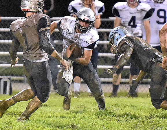 (Brad Davis/The Register-Herald) Valley's Austin Hess carries the ball during a muddy slogfest at Meadow Bridge Friday night in Meadow Bridge.