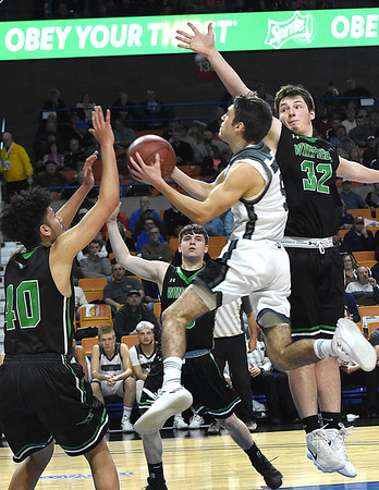 Shane Jenkins, of Wyoming East, drives between two Winfield defenders, Sean Hanshaw, left and Andrew Huff, Wednesday morning during the quarter-final game of the Class AA Boys State Basketball Tournament held at the Charleston Civic Center. Winfield won 68-65<br /> (Rick Barbero/The Register-Herald)