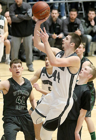 (Brad Davis/The Register-Herald) Westside's Corey Hatfield drives and scores as Wyoming East's Jacob Bishop (#40) and McQuade Canada defend during Big Atlantic Classic action Saturday the Beckley-Raleigh County Convention Center.