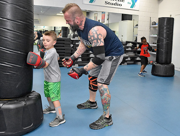 (Brad Davis/The Register-Herald) Six-year-old Jaxon Elswick works on his punch technique with encouragement from instructor Jamie Jesse during the first Kids Combat Cardio session to be held Sunday afternoon at the YMCA of Southern West Virginia. The one hour class will be held every Sunday in two age groups, kids 5-10 at 3:00 p.m., kids 11-18 at 4:00 p.m. and combines a fun workout environment with basic mixed martial arts training and techniques.