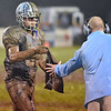(Brad Davis/The Register-Herald) Clean towels were at a premium as a Meadow Bridge player (number unidentifiable) hands one back to his coach during a muddy slogfest Friday night in Meadow Bridge.