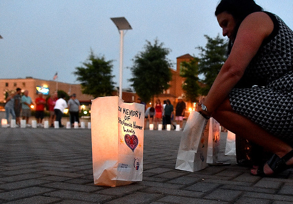 (Brad Davis/The Register-Herald) Friends and family gather around as they all light luminaries honoring those lost along with those still fighting cancer during the closing moments of the Relay For Life Friday night atop Beckley's Intermodal Gateway.