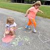 (Brad Davis/The Register-Herald) Six-year-old Madison Delp, left, puts the finishing touches on a bicycle as Autumn Colombo, 5, skips through her chalk obstacle course during Grandview Christian Church's Wacky Wednesday outdoor activity event at their property in Grandview where the old drag strip is.