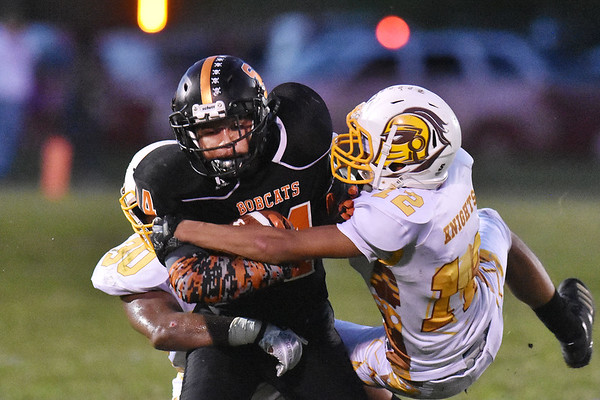 Summers County's Christian Pack (14) is tackled Mount View's Elijah Barner (30) and Jasauni Sizemore (12) during their high school football game Thursday in Hinton. (Chris Jackson/The Register-Herald)