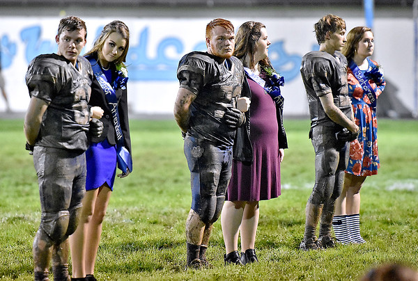 (Brad Davis/The Register-Herald) Mud-caked Meadow Bridge players stand with their clean escorts during the halftime homecoming ceremony of their slogfest with visiting Valley Friday night in Meadow Bridge.
