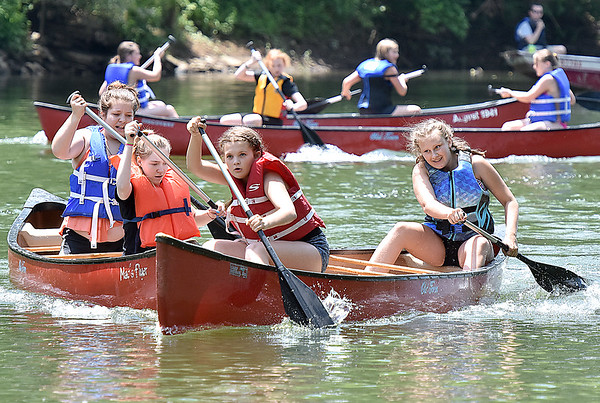 (Brad Davis/The Register-Herald) Participants of a 15 and under girls doubles heat try to avoid a collision with opponents on Greenbrier River as they paddle ferociously during the annual Alderson Canoe Races Sunday afternoon, part of the town's yearly 4th of July festivities.