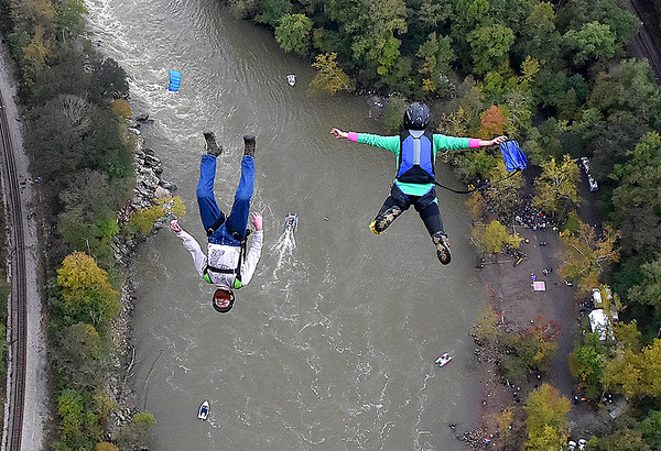 (Brad Davis/The Register-Herald) A pair of B.A.S.E. jumpers free fall towards the New River during Bridge Day Saturday in Fayetteville.
