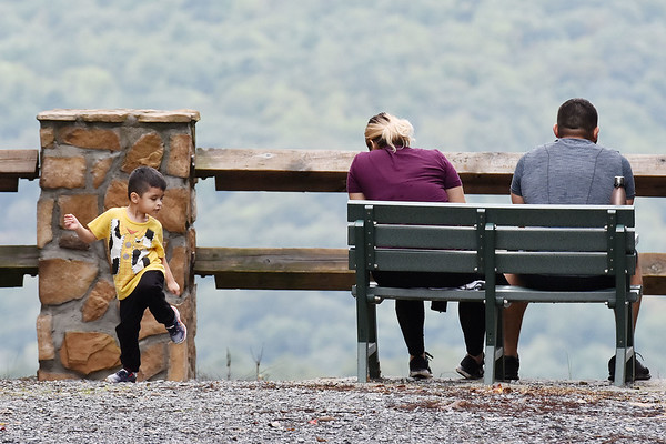 Martin Padilla, Jr., 2, plays as his parents, Cynthia and Martin Padilla, from Texas, look out at one of the overlooks at Pipestem State Park in Pipestem on Monday. (Chris Jackson/The Register-Herald)