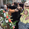 Nathaniel Jeter, of Beckley, former UBB miner, left, hugs Betty Harrah, of Beckley, sister of Steve Harrah who died in the explosion and Kim Lane with her grandson Brody lane, of Coolridge, family members of Richard Lane who also died in the explosion, stand in front of a wreath that was placed on the Raleigh County Courthoue lawn in memory of the 29 men who died in the UBB 2010 explosion.<br /> (Rick Barbero/The Register-Herald)