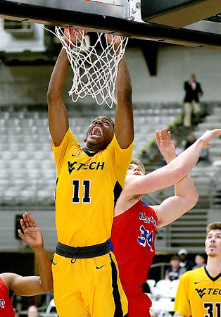 (Brad Davis/The Register-Herald) WVU Tech's Thomas Collins scores on a late-game dunk as Bluefield State's Gage Yesbeck defends Wednesday night at the Beckley-Raleigh County Convention Center.