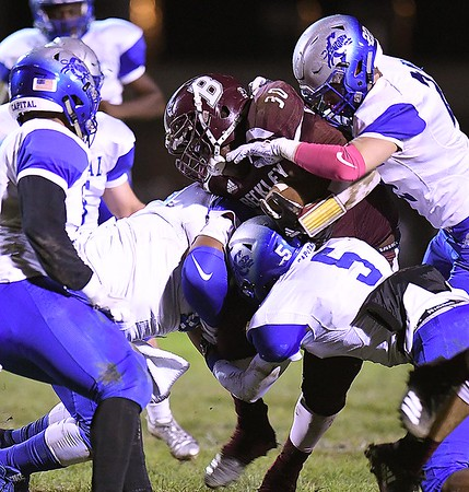 Martay Lee, of Woodrow Wilson, get tackled by Capitol defenders during game at Van Meter Stadium in Beckley Friday Night.<br /> (Rick Barbero/The Register-Herald)