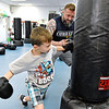 (Brad Davis/The Register-Herald) Eight-year-old Ethan Garten punches and punches some more as he's encouraged by instructor Jamie Jesse during the first Kids Combat Cardio session to be held Sunday afternoon at the YMCA of Southern West Virginia. The one hour class will be held every Sunday in two age groups, kids 5-10 at 3:00 p.m., kids 11-18 at 4:00 p.m. and combines a fun workout environment with basic mixed martial arts training and techniques.