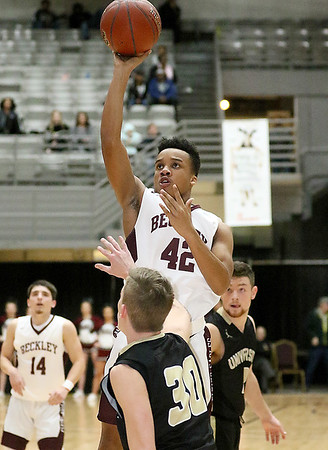 (Brad Davis/The Register-Herald) Woodrow Wilson's Richard Law puts up a short range shot as University's Austin Forbes defends during Big Atlantic Classic action Saturday the Beckley-Raleigh County Convention Center.