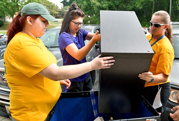 (Brad Davis/The Register-Herald) Incoming WVU Tech student Madilyn Bodkin, middle, gets some help lugging furniture items into a cart from current students and volunteers Kayla Hoff, left, and Logan Dudley as she moves into her dorm at University Hall during move-in day Sunday morning.