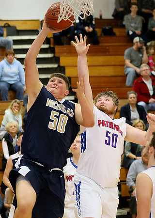 (Brad Davis/The Register-Herald) Nicholas County's Trey Milam powers his way to the basket as Midland Trail's Trevor Harrell defends during the Grizzlies' win over the Patriots Wednesday night in Hico.